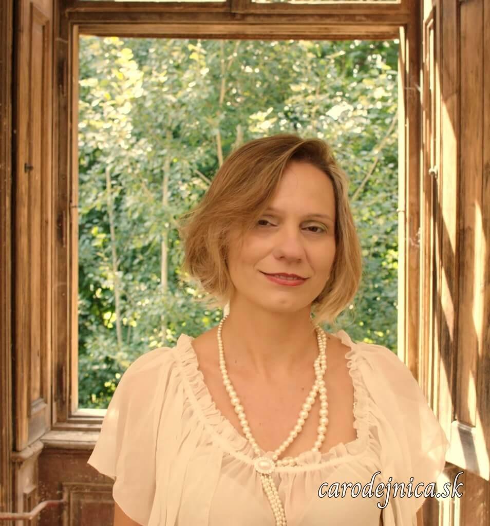 Žena v bielej blúzke s perlovým náhrdelníkom pred oknom z kaštieľa s výhľadom do záhrady