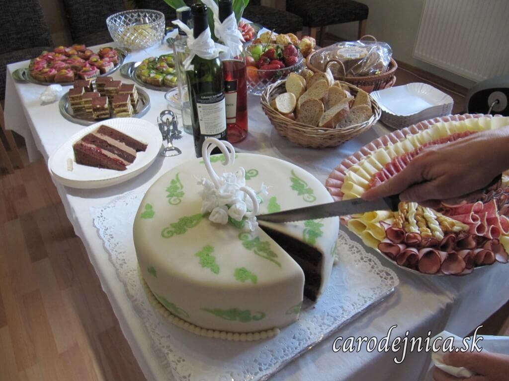Krájanie marcipánovej torty kakaovej na bohatom sviatočnom stole