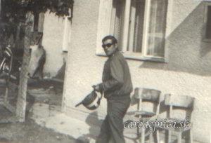 Stará fotografia muža v tmavých okuliaroch kráčajúceho po dvore s motorkárskou prilbou v ruke