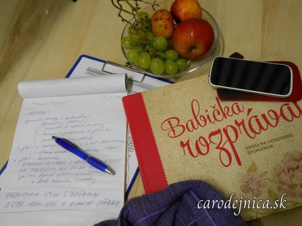 Kniha Babička rozprávaj, poznámky s perom, mobil a ovocie v miske