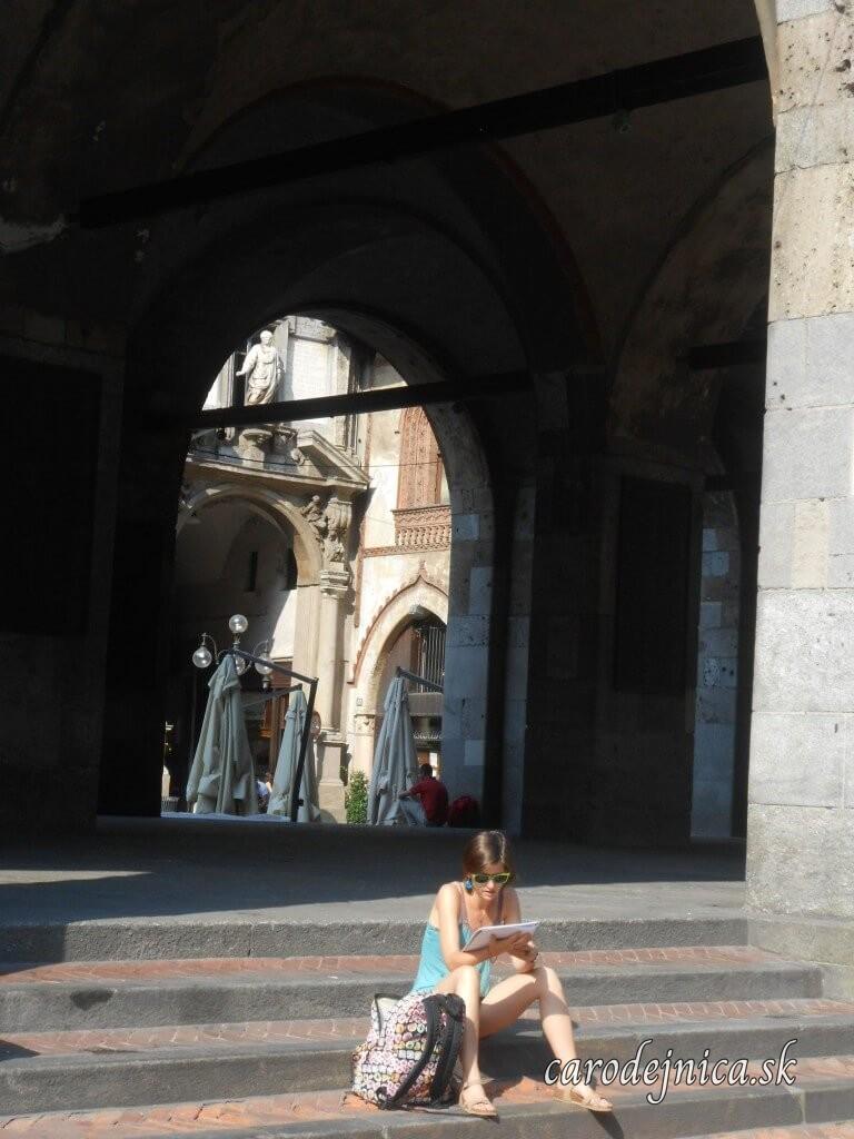 Dievča sediace na schodoch ku katedrále v Miláne, Taliansko