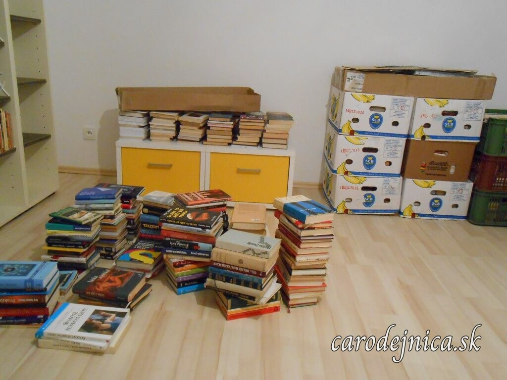 Knihy na podlahe a banánové krabice počas sťahovania sa