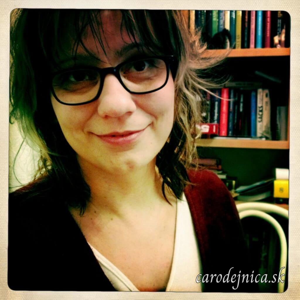 Žena v okuliaroch s čiernym rámom pred knižnicou