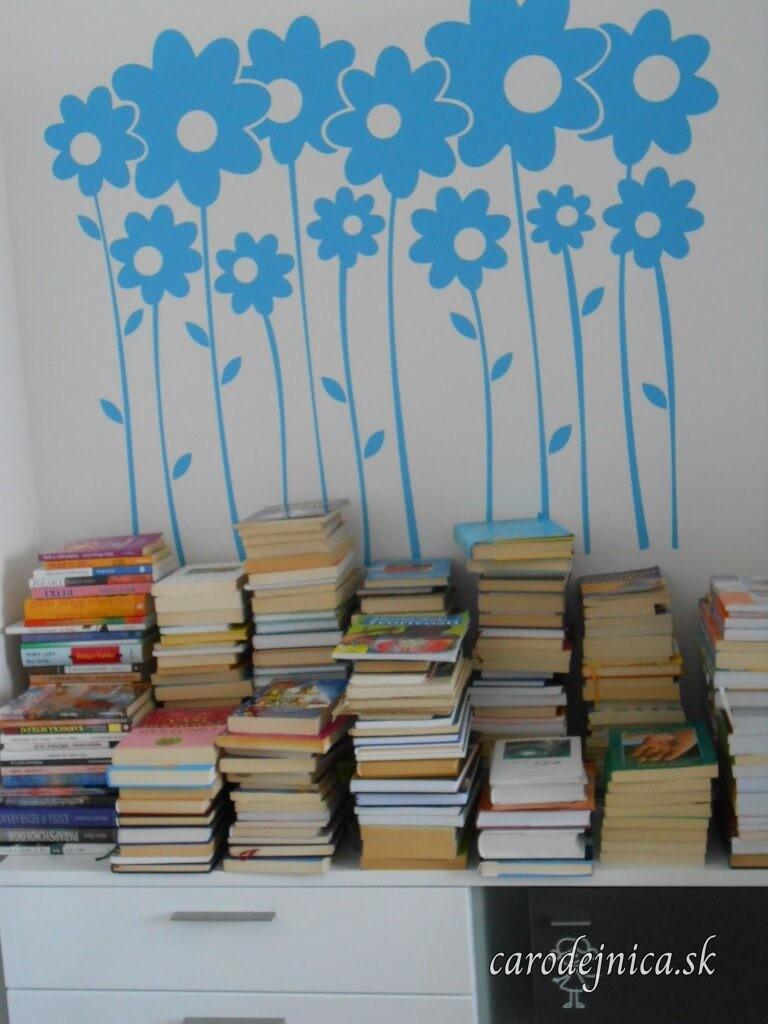 Modré nálepky kvetov na stene a pod nimi naskladané knihy na skrinke