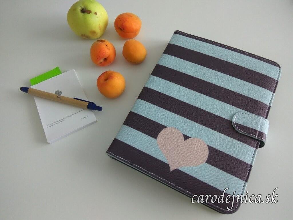 Pracovné zátišie na stole z laptopu v obale so srdiečkom, pero, návod a marhule s jablkom