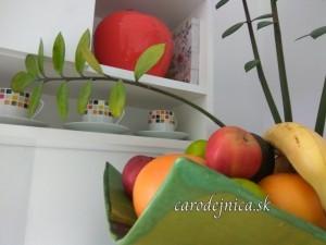 Ovocie v zelenej mise pri izbovej kvetine a polici so šálkami