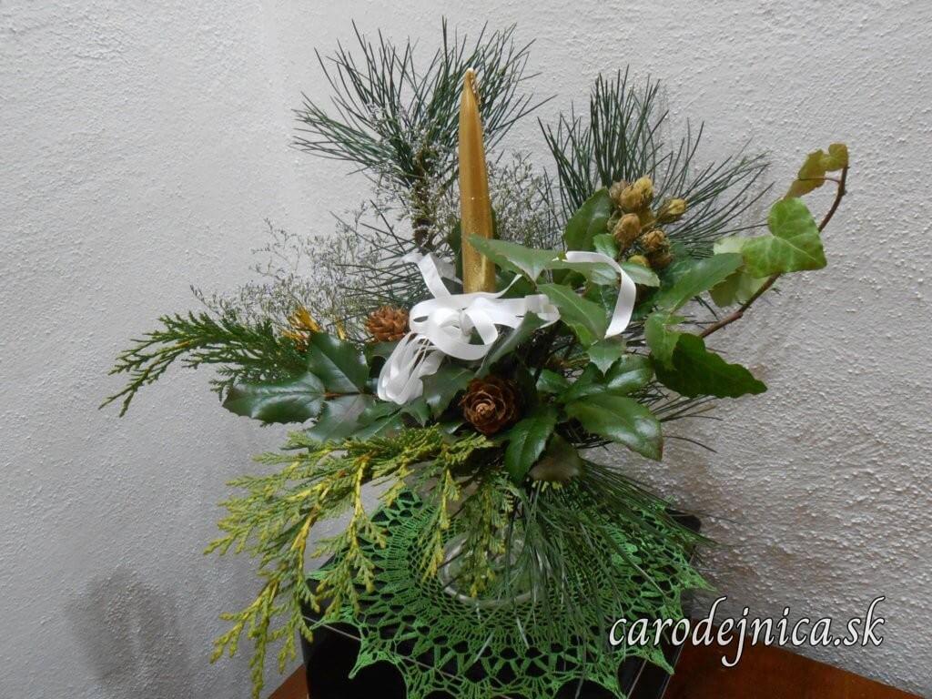tradičná vianočná ozdoba so zlatou sviečkou a bielou stužkou na vetvičke ihličnana