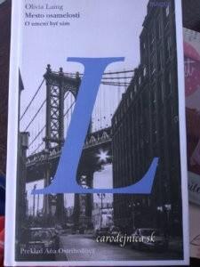 Titulka knihy Mesto osamelosti s veľkým modrým písmenom L a na pozadí most nad ulicou a budovou