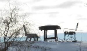 Dve lavičky a stôl pokryté snehom na kopci pod oblakmi