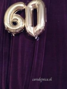 Nafúknuté balóny zlatej farby v tvare číslice 60 pred fialovým závesom