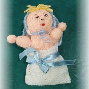 štrikovano-hačkované bábätko s modrou čiapočkou a modrou mašľou na perinke