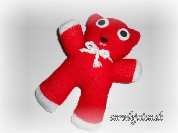 Štrikovaný medvedík červenej farby s veľkými očami a bielou mašľou