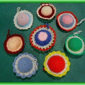 Rôznofarebné štrikovano-hačkované ihelníčky v počte kusov osem na zelenom podklade