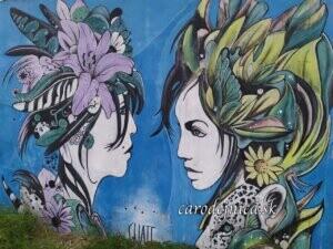 Dve ženy s kvetmi vo vlasoch na streetart
