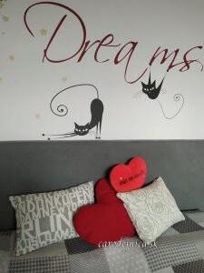 nápis dreams na stene nad posteľou s vankúšmi